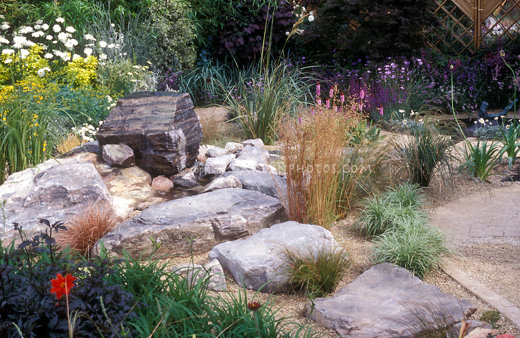 Ornamental grasses in a Feng Shui planting design. Rock garden boulders used, xeriscaping, low water use, dark leaved purple foliage dahlias, fence, patio, landscaping naturalistic style, ornamental grasses