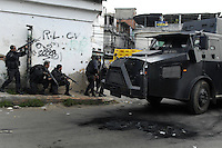 Policemen and an armored police vehicle participate at a operation at Vila Cruzeiro slum, Rio de Janeiro, Brazil, November 25, 2010. Authorities in Rio de Janeiro try to control a fourth day of violence apparently orchestrated by drug gang members who have attacked police stations and burned cars in Rio de Janeiro city as protest by traffickers after being forced from their turf by police occupations of more than a dozen slums in the past two years..(Austral Foto/Renzo Gostoli)
