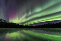 Aurora borealis reflects on a frozen lake in the Brooks Range mountains, Arctic, Alaska.