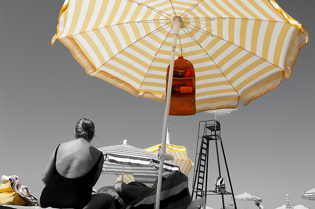 solitary Elderly women sitting under a yellow umbrella sun bathing