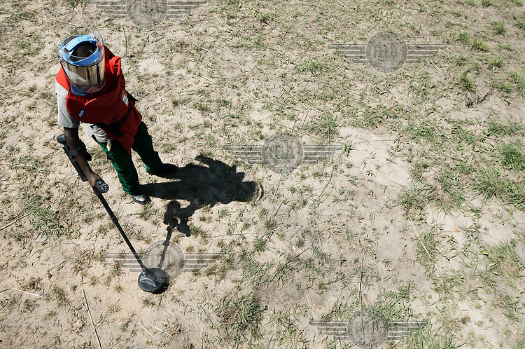 A member of a mine clearing team uses a detector in the search for unexploded ordinence in an area that experienced heavy fighting between SAF and SPLA forces between 1992 and 2004 when the  area was heavily mined.