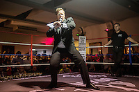 The ringmaster introduces a boxer at a white collar boxing event at the London Irish Centre where the 'Carpe Diem' boxing event is taking place. <br /> <br /> 'White-collar boxing' is a growing phenomenon amongst well paid office workers and professionals and has seen particular growth in financial centres like London, Hong Kong and Shanghai. It started at a blue-collar gym in Brooklyn in 1988 with a bout between an attorney and an academic and has since spread all over the world. The sport is not regulated by any professional body in the United Kingdom and is therefore potentially dangerous, as was proven by the death of a 32-year-old white-collar boxer at an event in Nottingham in June 2014. The London Irish Centre, amongst other venues, hosts a regular bout called 'Carpe Diem'. At most bouts participants fight to win. Once boxers have completed a few bouts they can participate in 'title fights' where they compete for a replica 'belt'.