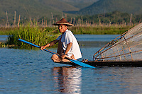 Myanmar, Burma.  Fisherman Looking for a Place to Set his Fishnet, Inle Lake, Shan State.