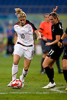 Aly Wagner, Marlies Oostdam. The USWNT defeated New Zealand, 4-0, during the 2008 Beijing Olympics in Shenyang, China.  With the win, the USWNT won group G and advanced to the semifinals.