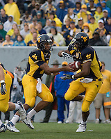 11 November 2006: West Virginia quarterback Pat White hands off to Jason Colson. The West Virginia Mountaineers defeated the Cincinnati Bearcats 42-24 on November 11, 2006 at Mountaineer Field, Morgantown, West Virginia..