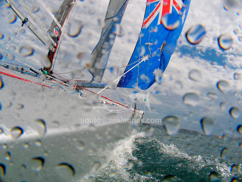 """Onboard a Tornado with the skipper Andrew Macpherson and crew Greg Lynch during a training session, Sydney Harbour..The Tornado is an olympic class sailing catamaran, with a crew of two. It was in the Olympic Games from 1976 through 2008, when multihulls were deselected for the 2012 games. It was designed in 1967 by Rodney March of Brightlingsea, England, with help from Terry Pierce, and Reg White, specifically for the purpose of becoming the Olympic catamaran. To increase its performance even further, the Tornado was modified in 2000, with a new sail-plan which included a Spinnaker and Spinnaker boom, as well as an increased sail area of the existing sails. An additional trapeze was also added, and the jib was made self tacking..The Tornado typically flies one of its two hulls; the crew balancing the boat with their own weight and by controlling the sails. With only one hull in the water, drag is significantly reduced. The Tornado also features an adjustable, rotating mast, which not only greatly improves the aerodynamics of the crucial leading edge of the sail, but also allows improved control over mast bend and thus mainsail flatness. For the high speeds and apparent wind directions seen by this high speed vessel, a flat sail profile is often required..The Tornado is said to be capable of speeds above 30 knots (56 km/h) reaching, and 18 knots (33 km/h) upwind, the Tornado class is often characterized as """"the Formula One of sailing""""."""
