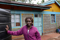 KENYA Thika near Nairobi, Simbi Roses is a fair trade rose flower farm which produces rose as cutting flowers for export to europe, worker Lucy Waithira Ngunga, 44 years old / KENIA Thika bei Nairobi, Simbi Roses ist eine fairtrade zertifizierte Blumenfarm die Rosen fuer den Export nach Europa anbauen, Pflueckerin Lucy Waithira Ngunga, 44 Jahre alt, vor ihrem Haus