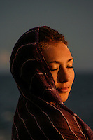 A woman with a striped pareo covering her head takes in the warmth of the sunset with her eyes closed, O'ahu.