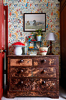 The door to the child's bedroom has been painted in a full gloss red adding warm tones and texture and complimenting the distressed chest of drawers