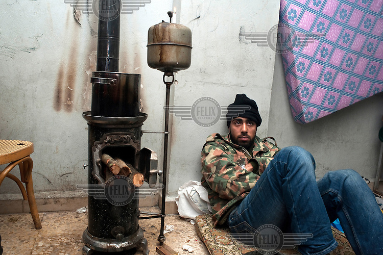 A young man sits next to a stove in a school building in Sarmada in Idlib governorate. He has found shelter in the town after fleeing intensifying fighting in neighbouring Hama governorate between the Syrian army and rebel fighters.Protests against the regime of Bashar al-Assad erupted in March 2011. Although initially peaceful, they were violently repressed by the Syrian army and police. In response to being ordered to shoot unarmed civilians, large numbers of men deserted and formed the core of the Free Syrian Army (FSA) which was soon joined by civilian volunteers. Since early 2012 the protest movement has escalated into an armed uprising that many consider a civil war. Sustained fighting is ongoing throughout Syria between the regular army and its allied militias and the Free Syrian Army as well as other anti-regime groups, some of which include foreign jihadists. ..