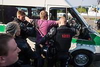 """Nach den pogromartigen Ausschreitungen gegen eine Fluechtlinsunterkunft im saechschen Heidenau am Freitag den 21. August 2015 durch Anwohnerinnen der Ortschaft, kamen am Samstag de 22. August 2015 ca. 250 Menschen in die Ortschaft um ihre Solidaritaet mit den Gefluechteten zu zeigen.<br /> Am Vorabend hatten Rassisten, Nazis und Hooligans sich zum Teil Strassenschlachten mit der Polizei geliefert um zu verhindern, dass Fluechtlinge in einen umgebauten Baumarkt einziehen. Ueber 30 Polizisten wurden dabei verletzt.<br /> Bis in die Abendstunden des 22. August blieb es trotz spuerbarer Anspannung um die Unterkunft ruhig. Im Laufe des Tages wurden immer wieder Gefluechtete mit Reisebussen gebracht was von den wartenenden Heidenauern mit Buh-Rufen begleitet wurde. Vereinzelt wurde auch """"Sieg Heil"""" gerufen, was die Polizei jedoch nicht verfolgte.<br /> Kurz vor 23 Uhr griffen Nazis und Hooligans dann wie am Vorabend die Polizei mit Steinen, Flaschen, Feuerwerkskoerpern und Baustellenmaterial an. Die Polizei mussten mehrfach den Rueckzug antreten, scheuchte den Mob dann von der Fluechtlingsunterkunft weg. Dabei wurden auch wieder Traenengasgranaten verschossen. Mindestens ein Nazi wurde festgenommen.<br /> Im Bild: Die Polizei hat den Fotojournalisten Nick Jaussi """"festgesetzt"""" nachdem er die Mehrzweckschusswaffe eines Beamten fotografiert hat. Die Beamten behaupteten, er habe Portraitaufnahmen von ihnen gemacht. Nach Aufnahme seiner Personalien und der Androhung einer Strafanzeige bei Veroeffentlichung der Aufnahmen wurde er wieder freigelassen.<br /> 22.8.2015, Heidenau<br /> Copyright: Christian-Ditsch.de<br /> [Inhaltsveraendernde Manipulation des Fotos nur nach ausdruecklicher Genehmigung des Fotografen. Vereinbarungen ueber Abtretung von Persoenlichkeitsrechten/Model Release der abgebildeten Person/Personen liegen nicht vor. NO MODEL RELEASE! Nur fuer Redaktionelle Zwecke. Don't publish without copyright Christian-Ditsch.de, Veroeffentlichung nur mit Fotografennennung"""