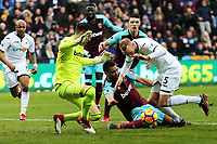 Winston Reid of West Ham (C) falls on the ground during a challenge between Adrian of West Ham (L) and Mike van der Hoorn of Swansea City (R) during the Premier League match between Swansea City and West Ham United at The Liberty Stadium, Swansea, Wales, UK. Saturday 03 March 2018