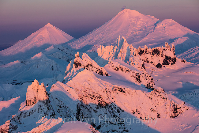 The Aghileen Pinnacles with Pavlof Sister, Pavlof Volcano, and Little Pavlof beyond at sunset. Izembek NWR, Alaska.