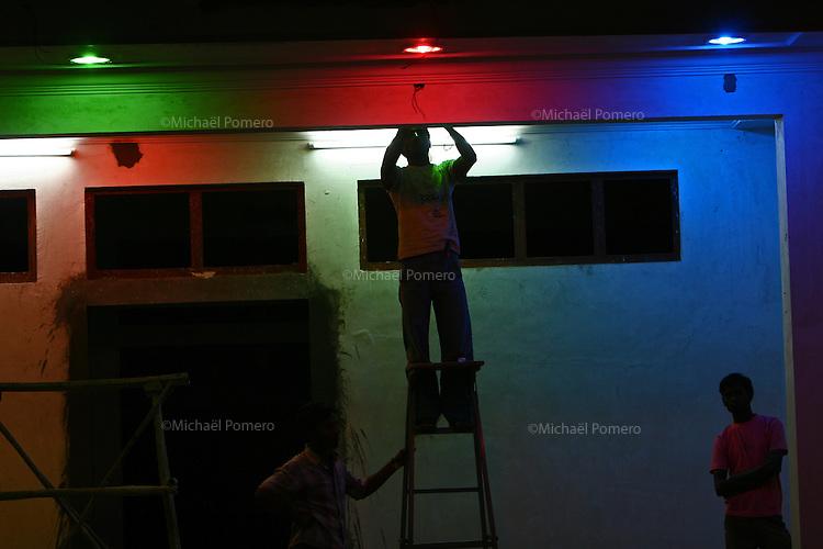 02.11.2008 Pushkar(Rajasthan)<br /> <br /> Men changing bulb in a shop.<br /> <br /> Hommes en train de changer une ampoule éléctrique dans un magasin.