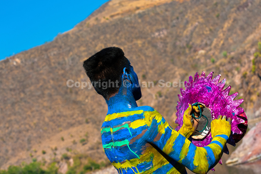"""A Cora Indian man, with body and face painted colorfully, paints his multi-colored hat before the religious ritual ceremony of Semana Santa (Holy Week) in Jesús María, Nayarit, Mexico, 22 April 2011. The annual week-long Easter festivity (called """"La Judea""""), performed in the rugged mountain country of Sierra del Nayar, merges indigenous tradition (agricultural cycle and the regeneration of life worshipping) and animistic beliefs with the Christian dogma. Each year in the spring, the Cora villages are taken over by hundreds of wildly running men. Painted all over their semi-naked bodies, fighting ritual battles with wooden swords and dancing crazily, they perform demons (the evil) that metaphorically chase Jesus Christ, kill him, but finally fail due to his resurrection. La Judea, the Holy Week sacred spectacle, represents the most truthful expression of the Coras' culture, religiosity and identity."""