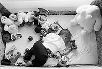 Switzerland. Canton Ticino. Lugano. Micaela Ruef is sleeping in her baby's bed surrounded by her plush toys. MODEL RELEASED. © 1997 Didier Ruef