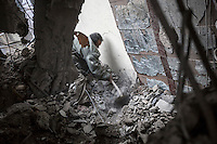 July 02, 2015 - Sana'a, Yemen: A Houthi militant looks for survivors at the rubble of a house building after it was hit by a fighter jet belonging to the Saudi coalition in the Yemeni capital Sana'a. Two children of the family were buried and died under the rubble during the missile attack while the mother and a two other children were taken to a nearby hospital. The mother and one of the children survived the attack as another one child died by his injuries. (Photo/Narciso Contreras)