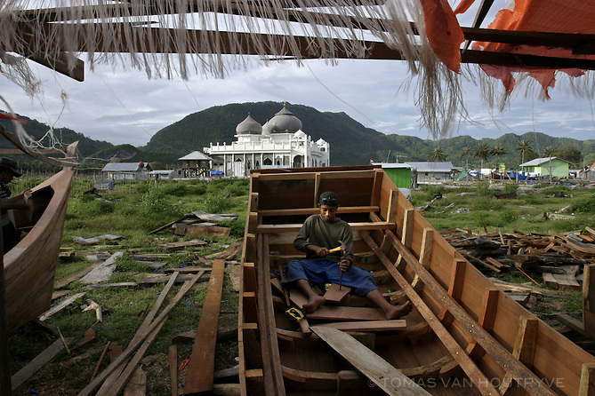 """A  man works on building a boat near the Rahmatullah Lampuuk mosque in the Lhoknga village near Banda Aceh, Indonesia on 23 October, 2005. The mosque was the only building left standing after tsunami waves hit the village on 26 Decemeber, 2004. Many months later, vegetation is growing again and rows of tents and temporary shelters have sprung up in the village. The main street has been renamed """"Bill Clinton George Bush Road"""" after the two former U.S. presidents visited the area.<br />"""