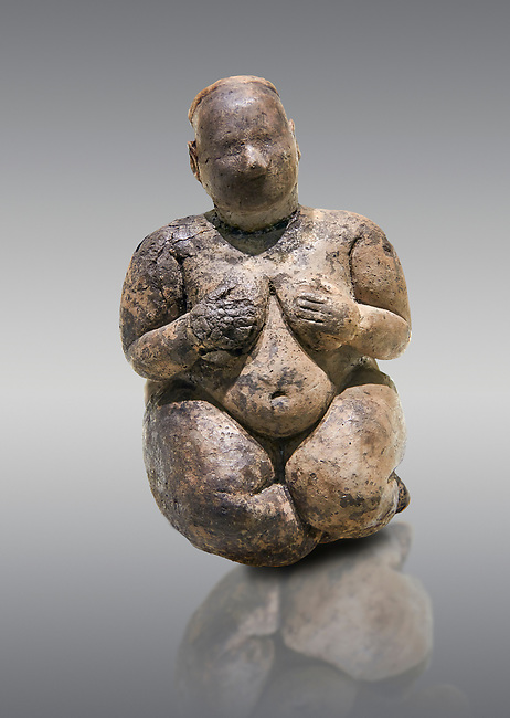 Seated terracotta goddess, probably a sign of fertility. Catalhoyuk Collections. Museum of Anatolian Civilisations, Ankara. Against a grey background