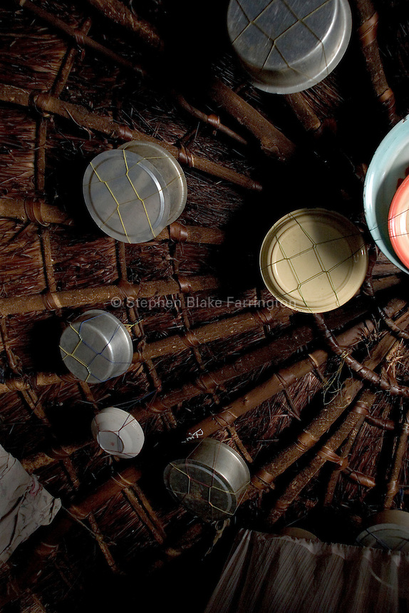 Cookware hangs from the roof of this hut located in the Unyama Internally Displaced PeopleÕs (IDPs) camp. In these camps space is limited and every inch available must be managed efficiently. The IDP camps of Northern Uganda formed when areas in the region became unsafe for civilians to live. Clean water, sanitation, food, employment, education, moral living, and human rights have almost been entirely depleted. Furthermore, congestion within the camps has contributed to major health and living problems. With 1.6 Ð 2 million people displaced and with an almost total lack of resources to care for them, the local peopleÕs very existence physically, emotionally and culturally is at stake. The war between the LordÕs Resistance Army and the Ugandan military has been transpiring since 1986. Thousands have been killed and abducted. Unyama (off Kitgum Road North) Gulu District, Uganda, Africa. December 2005 © Stephen Blake Farrington