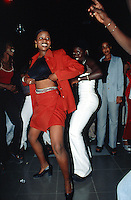 Senegal. Dakar. Night life at the Kily disco. Woman dances on mbalax music performed by the musician Thione Seck and his band. The girl lifts up her blouse, shows her stomach and belly in a sexy posture. © 2000 Didier Ruef
