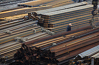 A worker stands near stacks of steel beams at a stock yard in Shanghai, China. China's government has already come up with plans to help the automobile and steel sectors, and is working to formulate overarching policies to help others, Premier Wen Jiabao said last Friday. China's steel industry has suffered greatly in the past year as demand and prices waned while most major steel manufactures were stuck with iron ore contracts made during the height of the commodities boom..05 Jan 2009