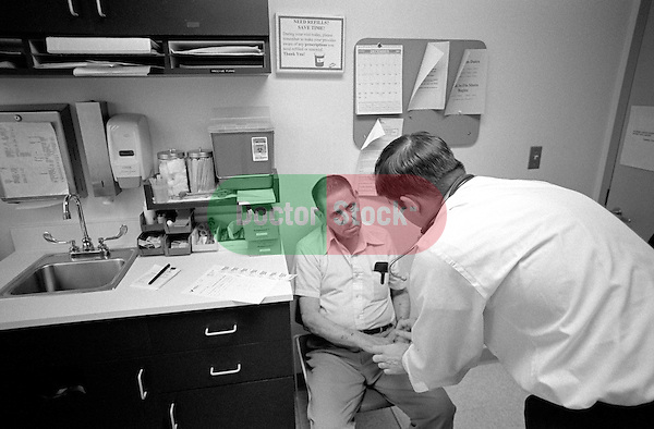 Elderly male patient listening as male doctor examines his hands