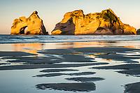 Sun sets on famous arches on Wharariki Beach on west coast of South Island, Nelson Region, South Island, New Zealand, NZ