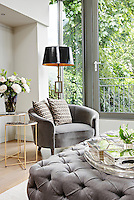 In a modern living room, a floor lamp stands behind a tub armchair with patterned cushions