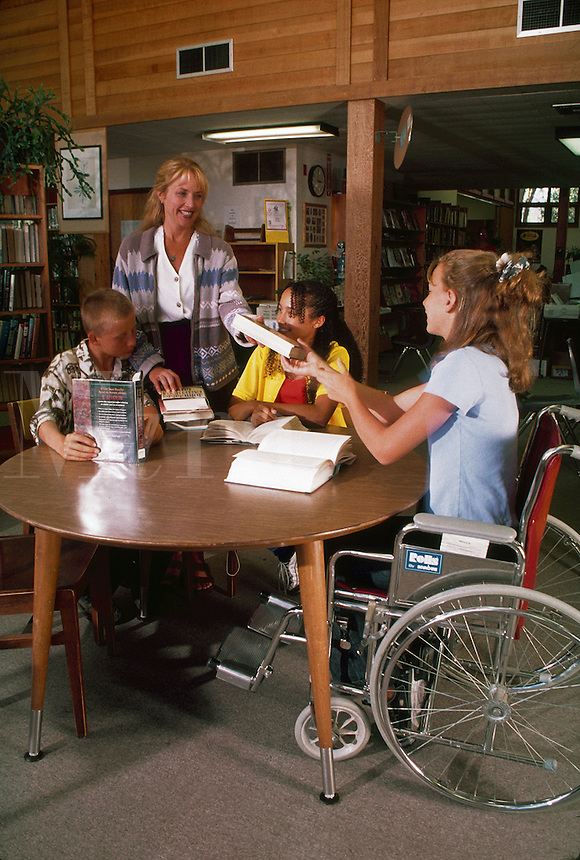Boy and two girls (one in wheelchair) with librarian in local library.