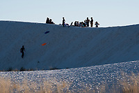 People walk among the dunes at White Sands National Monument near Alamogordo, New Mexico, USA, on Sat., Dec. 30, 2017.
