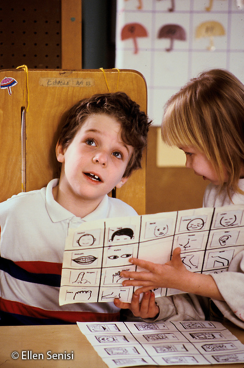 MR / Shenectady, NY.Yates Arts Magnet School / Special Education Class.Boy (7, autistic, non-verbal, ADHD, distractible) looks away as other student (Girl, 9, cystic fibrosis) helps him with sheets of symbols he uses to communicate..Mr: Cou1, Ngu1.PN#: 15122                      FC#: 21606-00117.scan from slide.©Ellen B. Senisi
