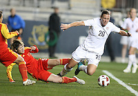 Abby Wambach #20 of the USA WNT falls after a tackle from Xinzhi Weng #5 of the PRC WNT during an international friendly match at PPL Park, on October 6 2010 in Chester, PA. The game ended in a 1-1 tie.