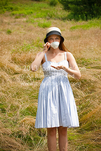 Young woman standing in field drinking tea