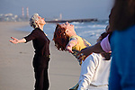 Senior females stretch out their arms in movement looking up and exercise in class on sandy Playa del Rey beach in Los Angeles, California
