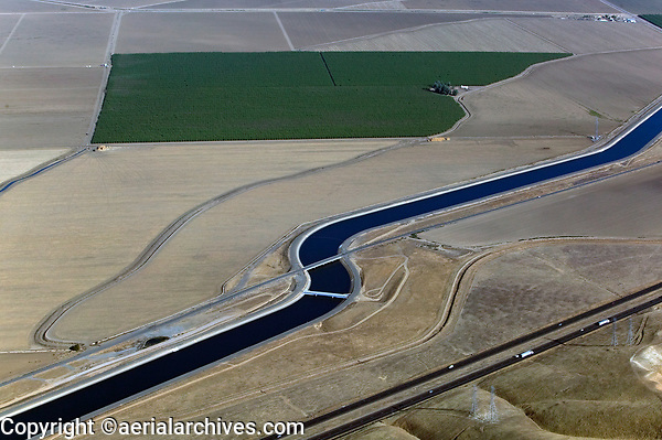 aerial photograph of the California Aqueduct, Central Valley, California running parallel to interestate I-5 and electric power transmission lines, an irrigated orchard in the background