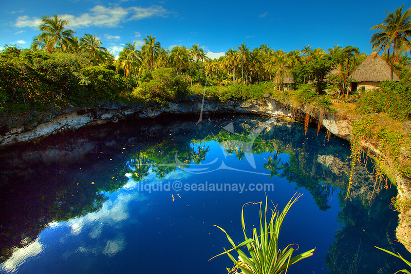"""Le Trou Bleu d'Anawa (Blue Hole of Anawa of Ouvéa in the Loyalty islands..Ouvéa (local pronunciation: [u?ve.a]) is a commune in the Loyalty Islands Province of New Caledonia, an overseas territory of France in the Pacific Ocean. The settlement of Fayaoué [fa?jawe], on Ouvéa Island, is the administrative centre of the commune of Ouvéa..Ouvéa is made up of Ouvéa Island, the smaller Mouli Island and Faiava Island, and several islets around these three islands. All these lie among the Loyalty Islands, to the northeast of New Caledonia's mainland..Ouvéa Island is one of the Loyalty Islands, in the archipelago of New Caledonia, an overseas territory of France in the Pacific Ocean. The island is part of the commune (municipality) of Ouvéa, in the Islands Province of New Caledonia..The crescent-shaped island, which belongs to a larger atoll, is 50 km (30 miles) long and 7 km (4.5 miles) wide. It lies northeast of Grande Terre, New Caledonia's mainland..Ouvéa is home to around 3,000 people that are organized into tribes divided into Polenesian, Melanesian and Walisian by ethnic descend. The Iaai language is spoken on the island..The two native languages of Ouvéa are the Melanesian Iaai and the Polynesian Faga Uvea, which is the only Polynesian language that has taken root in New Caledonia. Speakers of Faga Uvea have fully integrated into the Kanak society, and consider themselves Kanak..Ouvéa has rich marine resources and is home to many sea turtles, species of fish, coral as well as a native parrot, the Uvea Parakeet, that can only be found on the island of Ouvéa..A large crustacaen called a """"coconut crab"""" or crabe de cocotier can also be found on the islands. The large crabs live in palm tree plantations and live solely on a diet of coconuts that they crack open with their powerful claws. They are blue in colour and can grow to several kilos in size. They are a land based species and do not venture into the ocean.."""