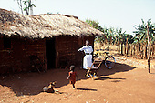 Near Ujiji, Tanzania. District nurse in white uniform with her bicycle outside a mud and thatch hut.