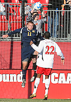 Zac MacMath #1 of the University of Maryland reaches over Jacob Wilson #11 of the University of California during an NCAA championship round of sixteen soccer match at Ludwig Field, on November 29, 2008 in College Park, Maryland. The match was won by Maryland 2-1