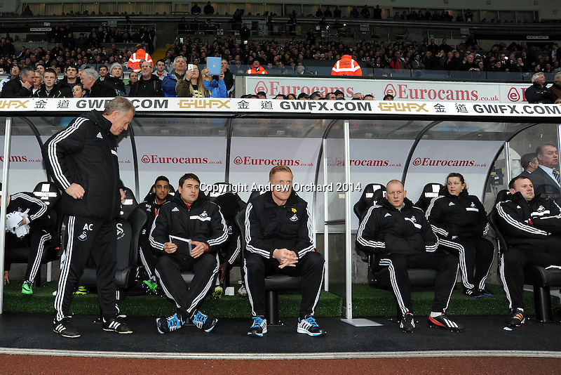 Swansea city's manager Garry Monk (c) with his coaching staff sits in dugout ahead of k/o. Barclays Premier league, Swansea city v Crystal Palace match at the Liberty Stadium in Swansea, South Wales on Sunday 2nd March 2014.