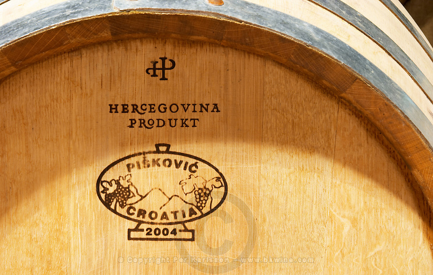 Oak barrel with stamp saying the winery's name and that the barrel is made from Croatian oak, Piskovic Croatia. Hercegovina Produkt winery, Citluk, near Mostar. Federation Bosne i Hercegovine. Bosnia Herzegovina, Europe.