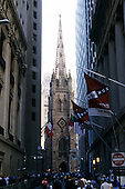New York, USA. Trinity Church amongst the tall office buildings on Wall Street with ornate stonework and tall steep steeple.