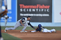 Columbia Fireflies shortstop J.C. Rodriguez (13) tags out a hard sliding Carlos Herrera (4) during a game against the Asheville Tourists at McCormick Field on June 18, 2016 in Asheville, North Carolina. The Tourists defeated the Fireflies 5-4. (Tony Farlow/Four Seam Images)