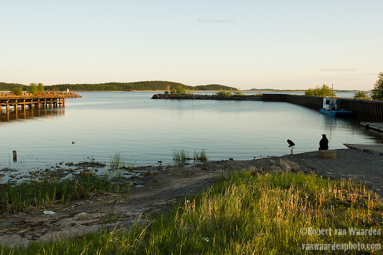 A mother and daughter play by the water in Fort Chipewyan