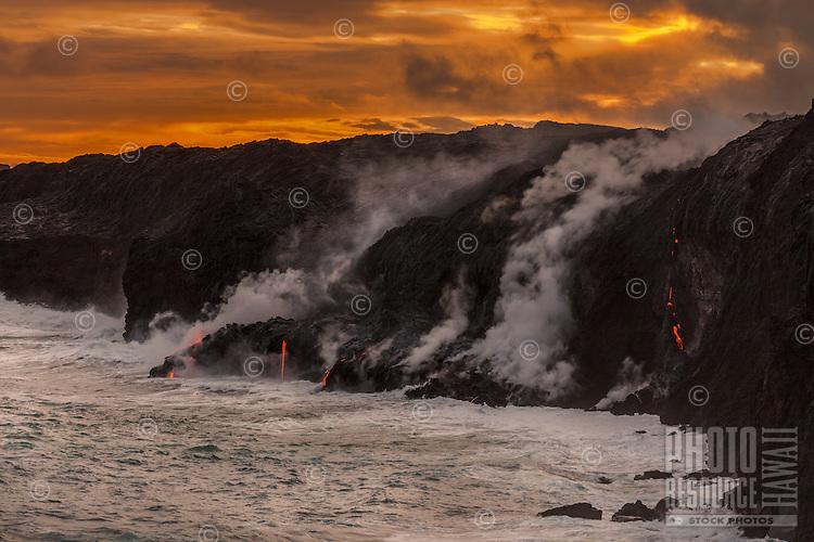 Sunset colors match the lava's intense orange glow near Kalapana on the Big Island of Hawai'i.