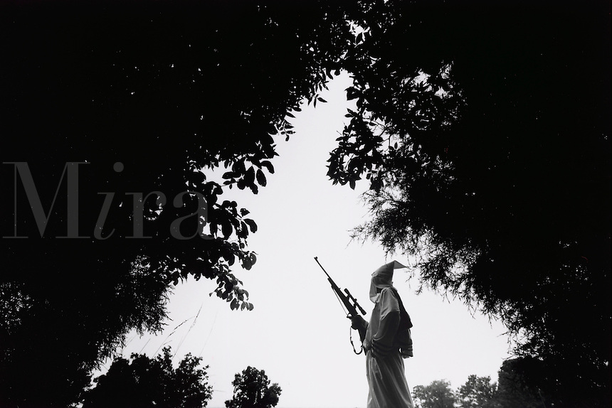 A guard for the Northwest Terrritory Knights of the Klu Klux Klan keeps watch in hooded attire, holding a rifle. Kentucky.