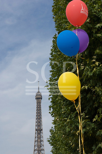 Paris, France. Coloured balloons in front of a green bush and the Eiffel Tower.