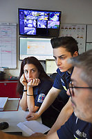 Switzerland. Canton Ticino. Pregassona. Control room  at Croce Verde Lugano's headquarters. The emergency doctor Daniele Speciale (R) explains to two paramedics how to read electrocardiogram's curves. They all work for theCroce Verde Lugano and wear blue uniforms. The woman (C) is a professional certified nurse, the other woman (L) is a volunteer specifically trained in emergency rescue. TheCroce Verde Lugano is a private organization which ensure health safety by addressing different emergencies services and rescue services. Volunteering is generally considered an altruistic activity where an individual provides services for no financial or social gain to benefit another person, group or organization. Volunteering is also renowned for skill development and is often intended to promote goodness or to improve human quality of life. Pregassona is a quarter of the city of Lugano.13.01.2018 © 2018 Didier Ruef