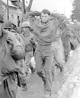 A lanky GI, with hands clasped behind his head, leads a file of American prisoners marching along a road somewhere on the western front.  Germans captured these American soldiers during the surprise enemy drive into Allied positions.  December 1944.  (Army)<br /> Exact Date Shot Unknown<br /> NARA FILE #:  111-SC-198240<br /> WAR & CONFLICT BOOK #:  1071