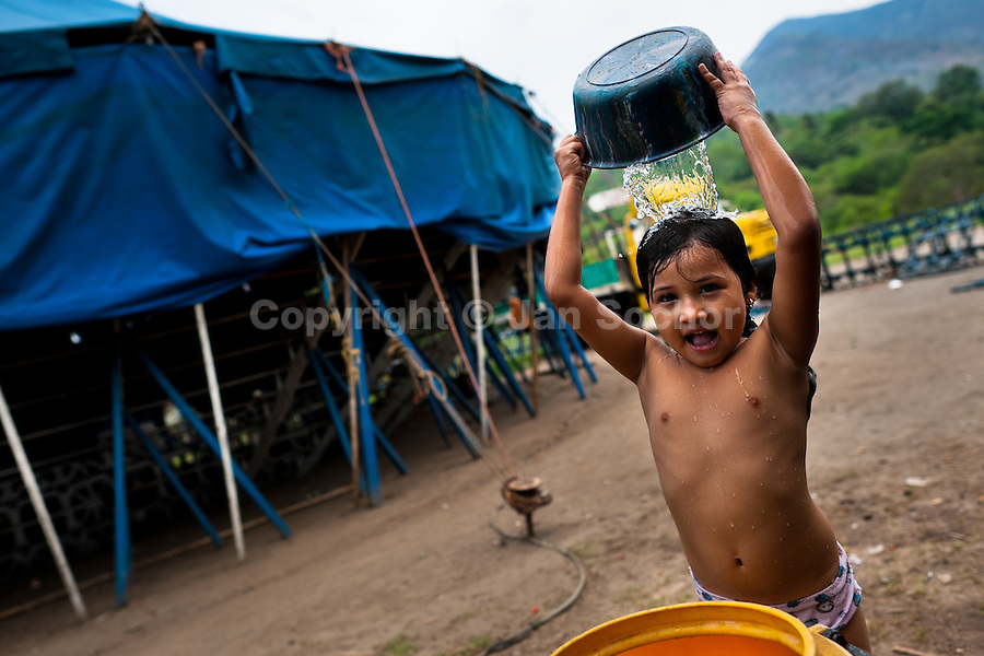 A Salvadorean girl has a bath in front of the tent of the Circo Brasilia, a family run circus travelling in Central America, 10 May 2011. The Circo Brasilia circus belongs to the old-fashioned traveling circuses with a usual mixture of acrobat, clown and comic acts. Due to the general loss of popularity caused by modern forms of entertainment such as movies, TV shows or internet, these small family enterprises balance on the edge of survival. Circuses were pushed away and now they have to set up their shows in more remote villages. The circus art and culture is slowly dying in Latin America.